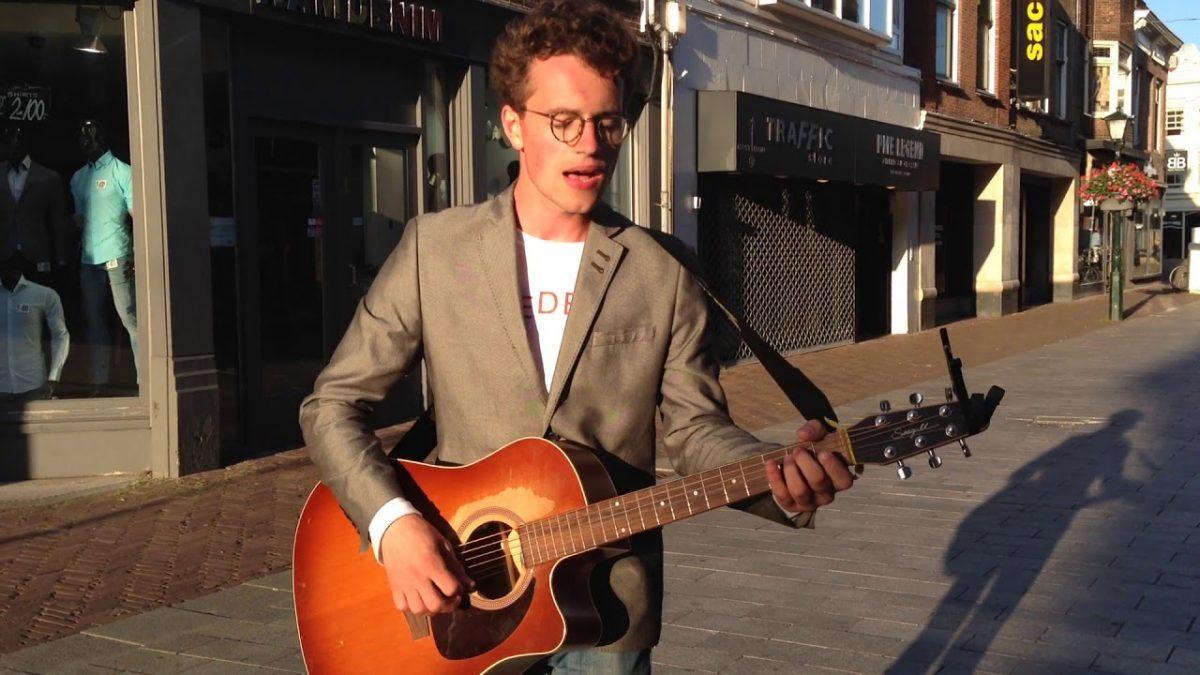 Owen Neid playing guitar on the street